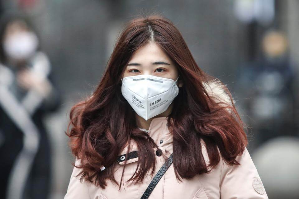 Woman in Wuhan Walking with face mask January 2020